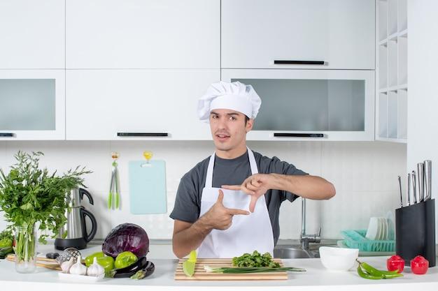 Вид спереди молодой шеф-повар в униформе, делая знак камеры