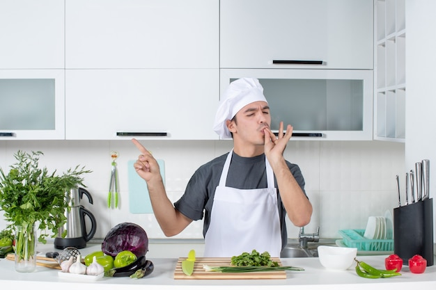 Вид спереди молодой шеф-повар в униформе, делающий поцелуй шеф-повара на кухне