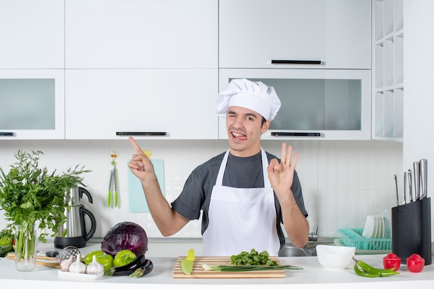Вид спереди молодой шеф-повар в униформе, высунув язык, делая знак ок