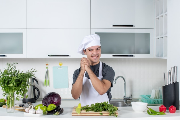 Front view young chef in uniform clasping hands