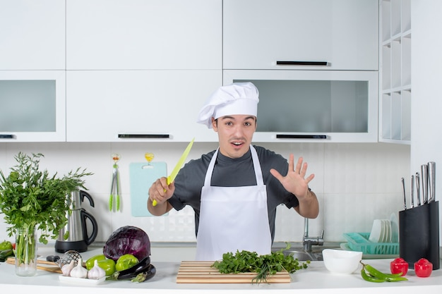 Front view young chef in uniform holding knife cutting greens