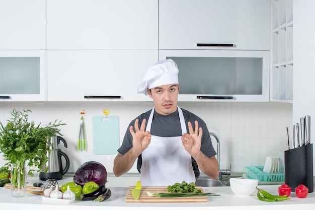 Front view young chef in uniform making okey sign in kitchen