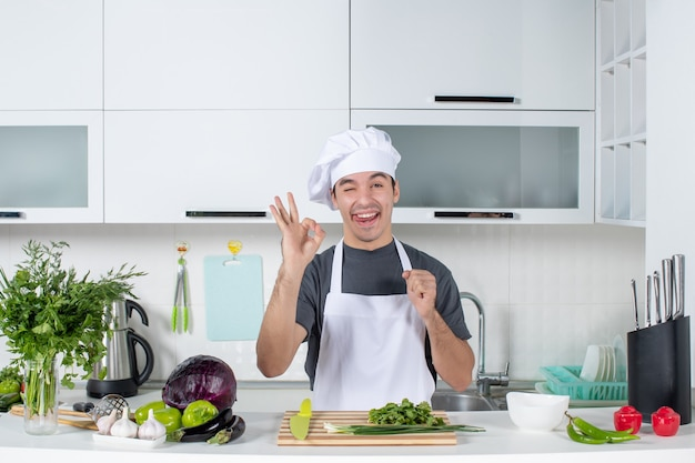 Front view young chef in uniform making okey sign sticking out tongue