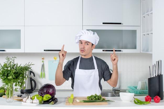 Giovane chef di vista frontale in uniforme che punta al soffitto