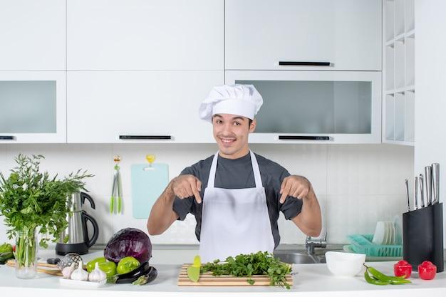 Giovane chef di vista frontale in uniforme che indica i verdi sul tagliere