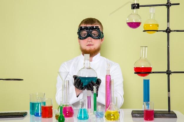 Giovane chimico di vista frontale che fa nuovi esperimenti in occhiali protettivi