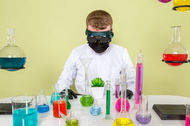 Молодой химик, вид спереди, экспериментирует с растением в защитных очках