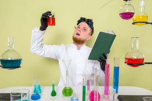 Il giovane chimico di vista frontale trova finalmente la nuova formula con la sostanza chimica rossa