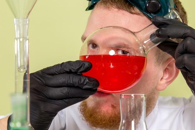 化学物質に非常に近いところを見ている若い化学者の正面図