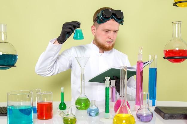 Giovane chimico di vista frontale che legge sulla sostanza chimica blu-chiaro