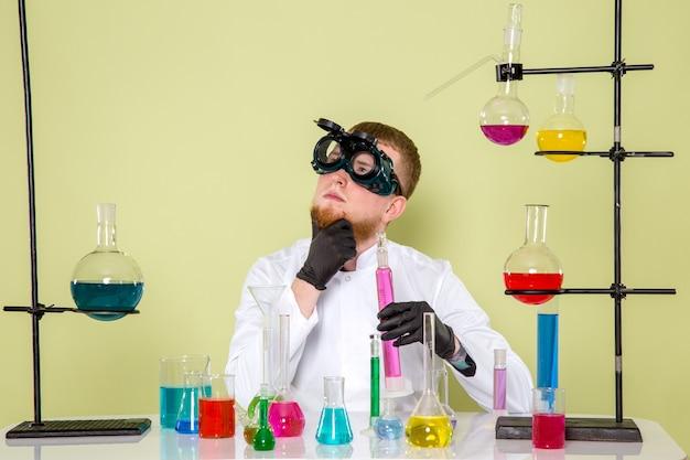 Вид спереди молодой химик думает о научных экспериментах