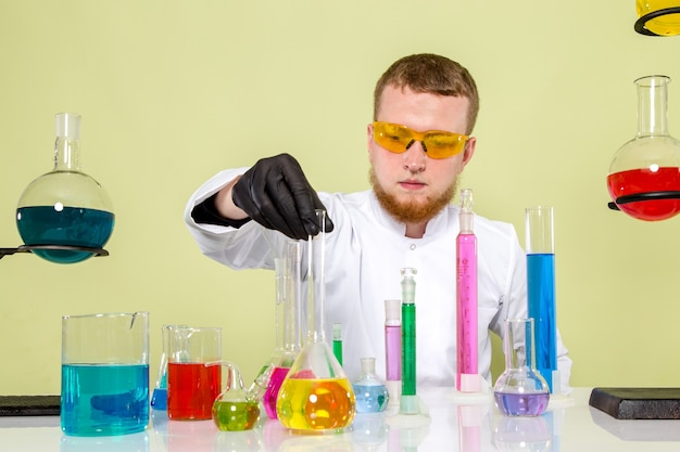 Front view young chemist using different flasks in a lab