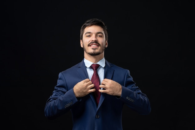 Front view of young and confident bearded man in suit straightening his tie on dark wall