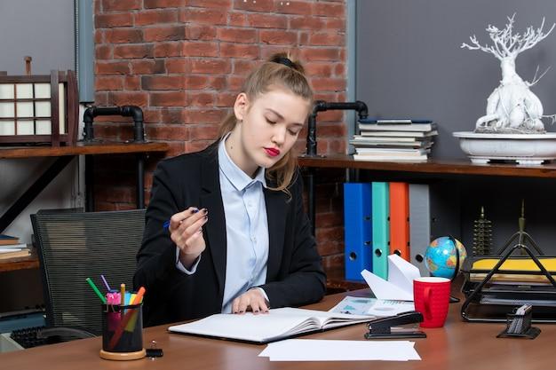 Vista frontale della giovane assistente femminile sicura di sé seduta alla sua scrivania e leggendo un documento in ufficio