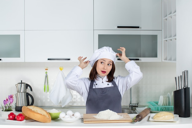 Front view of young confident female chef in uniform touching her hat in the white kitchen