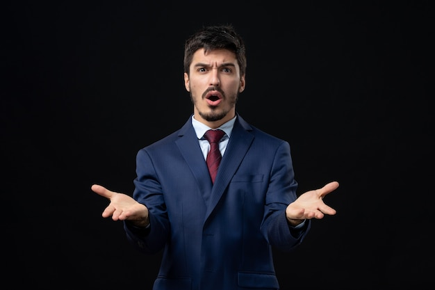 Front view of young confused man in suit asking something with suspicious facial expression on isolated dark wall