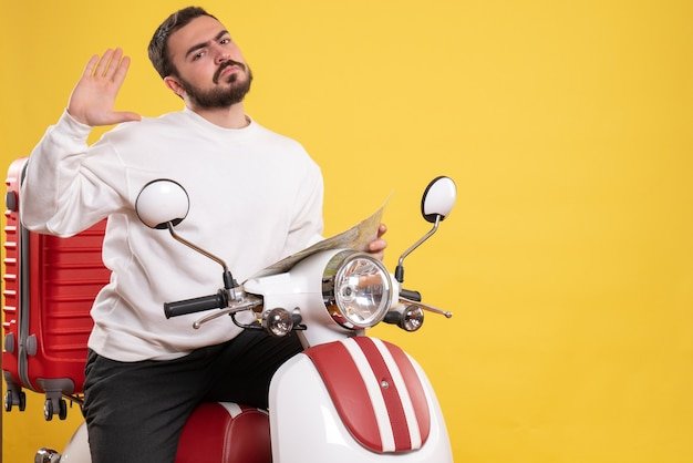 Vista frontale di un giovane uomo in viaggio confuso seduto su una motocicletta con la valigia sopra che tiene una mappa su sfondo giallo isolato isolated