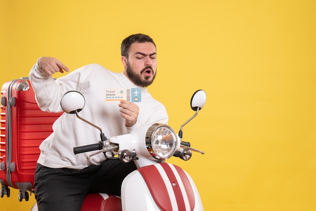 Front view of young confused travelling man sitting on motorcycle with suitcase on it holding ticket on isolated yellow background