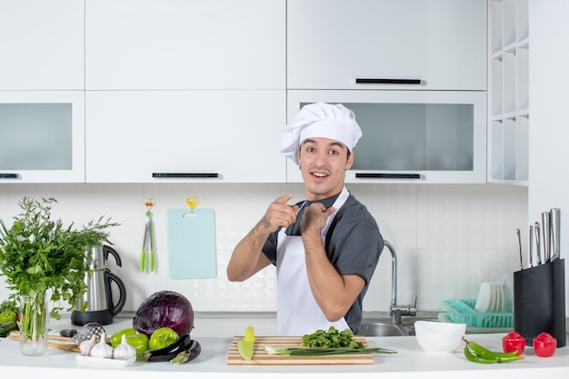 Giovane cuoco di vista frontale in uniforme che indica alla macchina fotografica