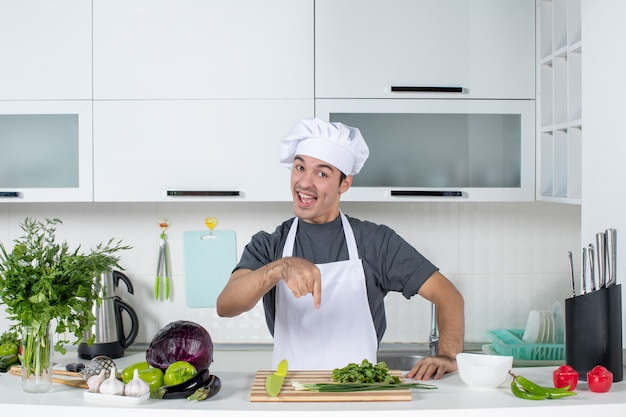 Vista frontale giovane cuoco in uniforme che punta al verde sul tagliere