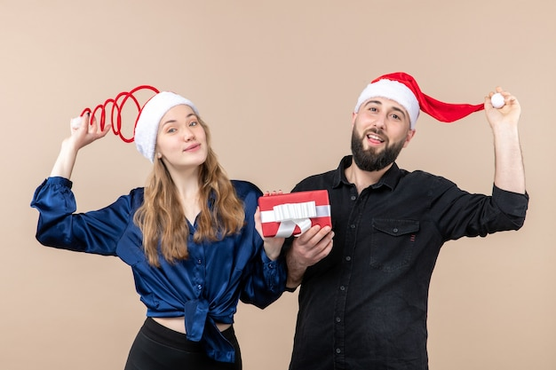 Front view young couple both holding males present on pink background gift holiday photo new year christmas