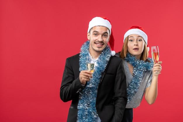 赤いデスクパーティーのクリスマスの愛で新年を祝う正面図の若いカップル