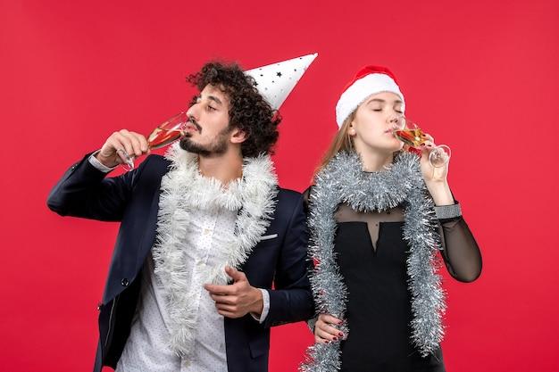 Вид спереди молодая пара празднует новый год на красной стене, праздник рождественской любовной вечеринки