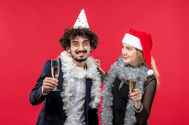 Вид спереди молодая пара празднует новый год на красной стене праздник любви рождественская вечеринка
