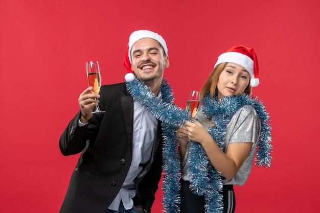 赤い壁の愛のクリスマスの色で新年を祝う正面図の若いカップル