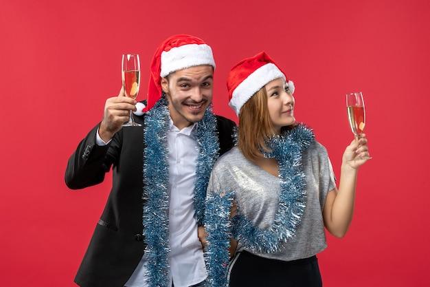 Вид спереди молодая пара празднует новый год на красной стене любовная вечеринка рождество