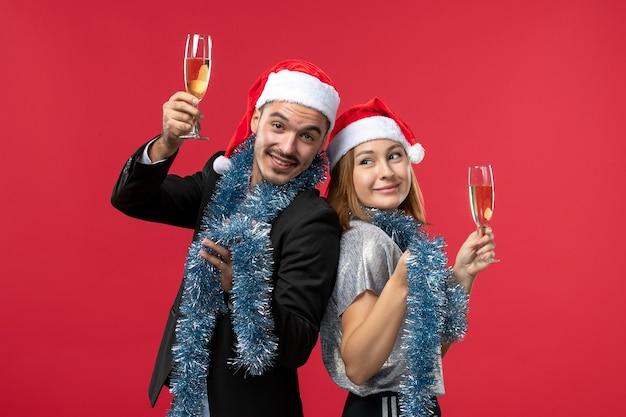 Вид спереди молодая пара празднует новый год на красной стене, вечеринка, любовь, рождество