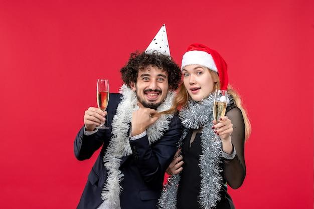 Вид спереди молодая пара празднует новый год на красном столе, праздник рождественской любовной вечеринки