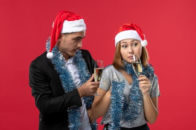 Вид спереди молодая пара празднует новый год на красном столе любовная вечеринка рождество