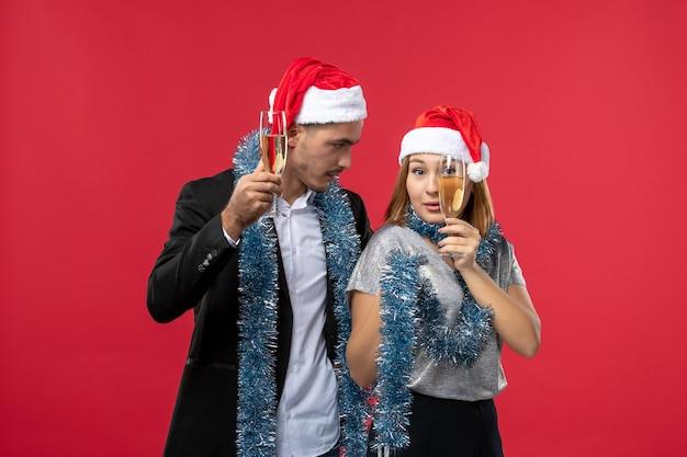 Вид спереди молодая пара празднует новый год на красном столе, вечеринка, любовь, рождество