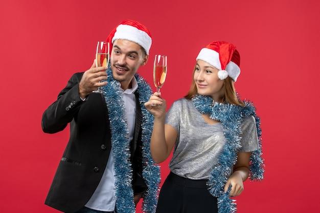 赤い床の色の愛のクリスマスで新年を祝う正面図の若いカップル