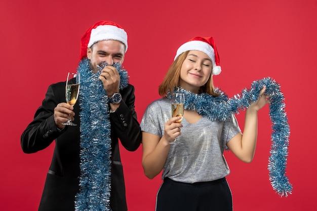 赤い床の休日の愛のクリスマスに新年を祝う正面図の若いカップル