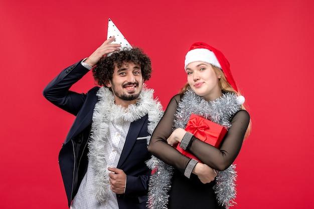 赤い壁のクリスマスの愛の休日に新年を祝う正面図の若いカップル