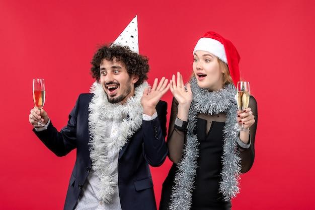 Вид спереди молодая пара празднует новый год на красной стене рождественская вечеринка любви