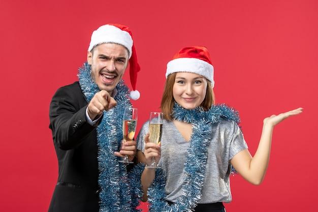 赤い壁のクリスマスの愛のパーティーで新年を祝う正面図の若いカップル