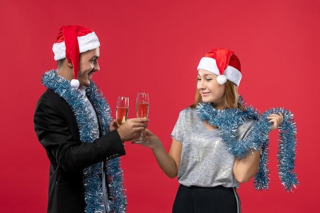 赤い壁の色の愛のクリスマスで新年を祝う正面図の若いカップル