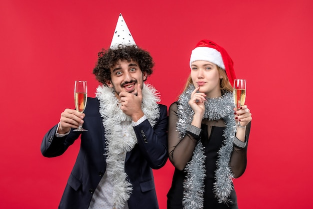 赤い壁の休日のクリスマスの愛のパーティーで新年を祝う正面図の若いカップル