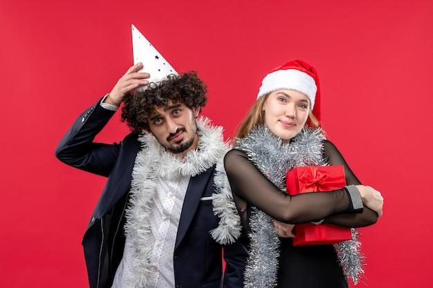 赤い壁の休日のクリスマスの愛で新年を祝う正面図の若いカップル