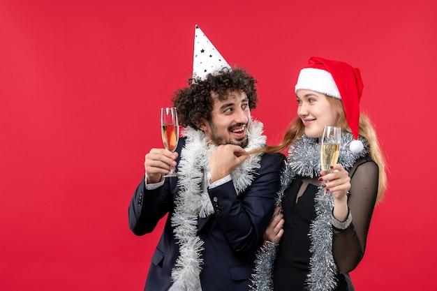 赤い壁の休日の愛のクリスマスパーティーで新年を祝う正面図の若いカップル