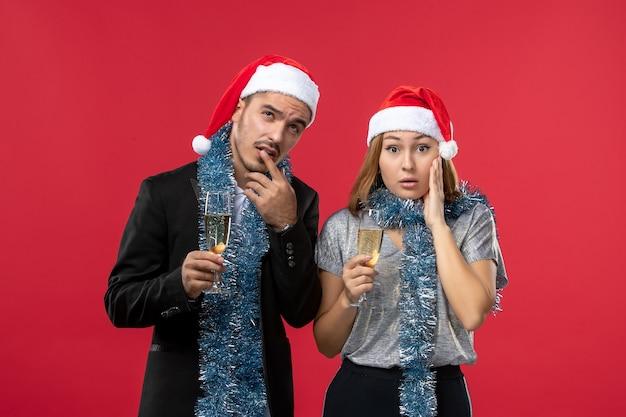 赤い壁の休日の愛のクリスマスに新年を祝う正面図の若いカップル