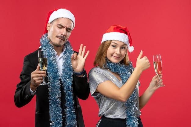 Вид спереди молодая пара празднует новый год на красной стене любовь рождественская вечеринка напитки