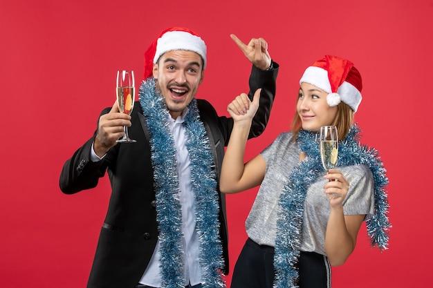 빨간 벽에 새 해를 축 하하는 전면보기 젊은 부부 사랑 크리스마스