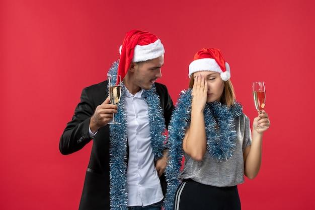 赤い壁の愛のパーティーのクリスマスに新年を祝う正面図の若いカップル