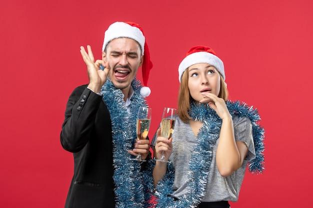Вид спереди молодая пара празднует новый год на красной стене вечеринки рождественская любовь