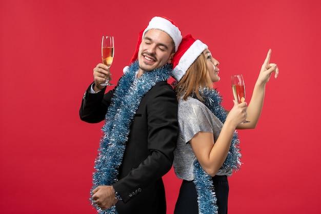 赤い壁のパーティーで新年を祝う正面図の若いカップルはクリスマスが大好きです