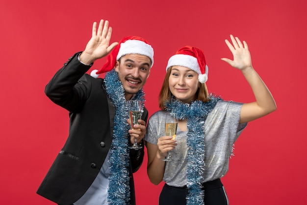 赤い壁で新年を祝う正面図の若いカップルはクリスマスの色の休日が大好きです